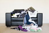 stock photo of dirty-laundry  - Housework concept of a large pile of laundry dumped on the couch waiting to be folded and put away - JPG