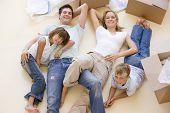 Família deitado no chão por abrir caixas em nova casa sorrindo