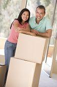 Casal com caixas na nova casa sorrindo