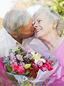 Husband Giving Wife Flowers Outdoors Kissing And Smiling