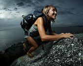 stock photo of climbing wall  - Hiker with backpack climbing natural rocky wall on a dark cloudy background - JPG