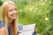 stock photo of bible story  - A young attractive woman laying in the grass outside reading the book the Bible - JPG