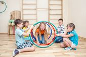 Cheerful kids playing with hula hoops in a school gym