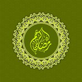 Arabic Islamic calligraphy of text Ramadan Kareem in green floral decorated background.