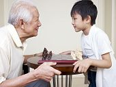 stock photo of grandpa  - grandpa and grandson looking into each other - JPG