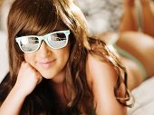 sexy brunette laying on bed with sunglasses