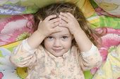 Two-year-old Girl Lying On The Bed And His Head In His Hands, Looks Fun In The Frame