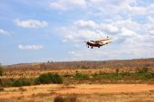 stock photo of cessna  - Small cessna aircraft takeoff in Cenral Africa from ground runway. Dry savanna lanscape, red african ground.