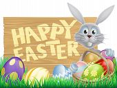 stock photo of peep  - Easter wood sign reading Happy Easter with the Easter bunny and decorated Easter eggs - JPG