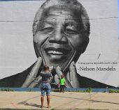 Unidentified family taken picture in the front of Nelson Mandela mural
