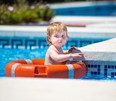 smiling cute little baby swims with a lifeline in the pool in  summer
