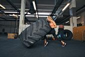 foto of strength  - Fit female athlete working out with a huge tire turning and flipping in the gym - JPG