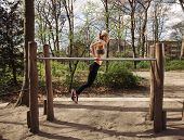 picture of dipping  - Side view of muscular young woman doing triceps dips on parallel bars at park - JPG