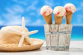 Raspberry ripple ice creams with sunhat and beach blur background