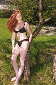 Beautiful redhead teenager in a black bikini