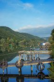 stock photo of moselle  - Image of the Moselle River with jettys boats and a lush green forest - JPG