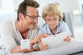 foto of 7-year-old  - Father and son playing with tablet and smartphone - JPG