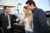 stock photo of 35 to 40 year olds  - Salesman in car dealership giving keys to clients - JPG