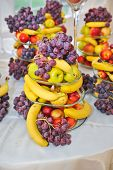 Fruits arrangement on restaurant table. Wedding decoration with fruits, bananas, grapes and apples.