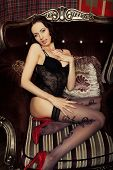 stock photo of panty hose  - Glamour brunette wearing black lingerie posing on chair - JPG