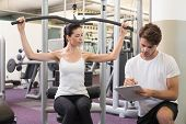 Fit brunette using weights machine for arms with trainer taking notes at the gym