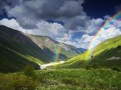 Summer landscape with river in a mountain valley. View from the beautiful sky and rainbow above the mountains