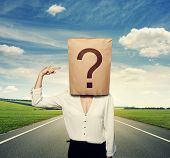 businesswoman with paper bag on the head pointing at question