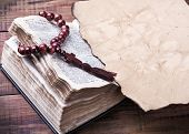 Bible With Rosary And Old Burnt Piece Of Paper
