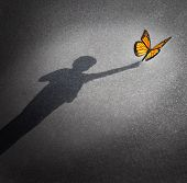 stock photo of innocence  - Wonder and discovery concept as a shadow of a child reaching out to touch a butterfly as an education and learning symbol of childhood curiosity and innocence towards nature and the world around them - JPG