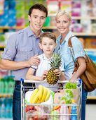 Half-length portrait of family in the market. Son keeps pineapple over the shopping trolley full of