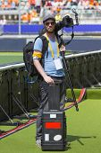 A sports photographer posing along a sportsfield with his camera on his shoulder with a monopod moun