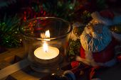 Christmas background tea candles and toy Santa