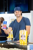 Portrait of happy male worker holding drink with popcorn at cinema concession stand while colleague working in background