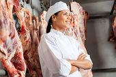 Happy mid adult female butcher standing arms crossed in slaughterhouse