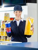 Portrait of happy female worker holding popcorn and drink at cinema concession counter
