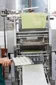 Cropped image of female chef holding ravioli pasta tray by machine at commercial kitchen