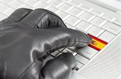 Hacking Spain Concept With Hand Wearing Black Leather Glove Pressing Enter Key With Flag Overlaid