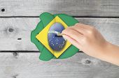 Brazil Saving Concept With Little Hand Dropping A Coin Into Piggy Bank Overlaid With Brazilian Flag