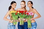 Three Sexy Topless Smiling Women in Jeans Covering their Chests with Fresh Beautiful Flowers While Looking at the Camera. Isolated on White Background.