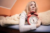 Unhappy Girl In Bed With Alarm Clock