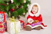 pic of santa baby  - Baby in Santa costume at the Christmas tree with gifts - JPG