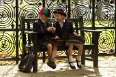 Brother And Sister Eating On Wooden Bench