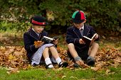 Brother And Sister Reading Among Autumn Leaves
