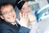 Smiling Couple In A Car Holding Hands With Rings On The Fingers
