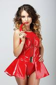 Alluring Woman In Red Rubber Outfit Biting Chili Pepper