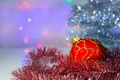 Red Christmas ball under the tree and tinsel