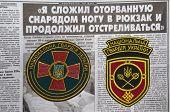 Kiev,Ukraine.Oct 16.Illustrative editorial.Ukranian National Guard  chevrones .Newspaper with heroic story of soldier as background.At October 16,2014 in Kiev, Ukraine