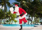 christmas, holidays, travel and people concept - man in costume of santa claus running with clock showing twelve over swimming pool on tropical beach background