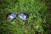 a pair of aviator sunglasses on green grass with blue cloudy sky reflecting in the mirror lenses