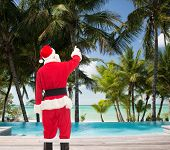 christmas, holidays and people concept - man in costume of santa claus pointing finger from back over tropical beach and swimming pool background